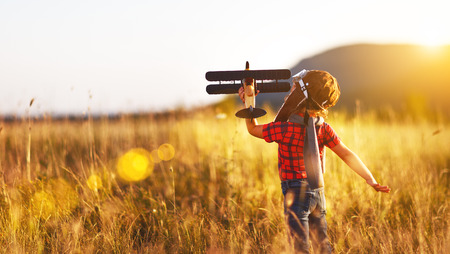 Child pilot aviator with airplane dreams of traveling in summer in nature at sunset Stock Photo