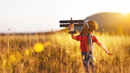 Kind proef vliegenier met vliegtuig dromen van het reizen in de zomer in de natuur bij zonsondergang