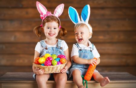 Gelukkige jonge geitjes jongen en meisje verkleed als Paashazen lachen met een mand met eieren op houten achtergrond Stockfoto