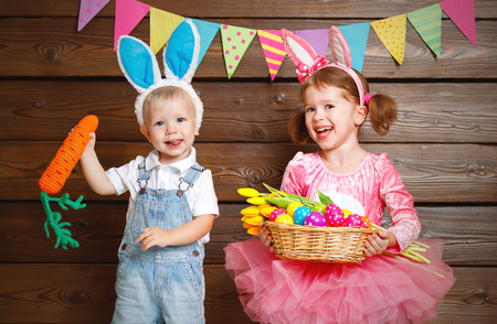 niños sonriendo: Happy kids boy and girl dressed as Easter bunnies laughing with basket of eggs on wooden background