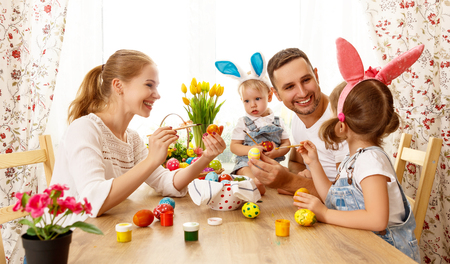 traditional: Happy easter! family mother, father and children having fun paint and decorate eggs for holiday