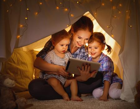 Gelukkig gezin moeder en kinderen spelen in tablet pc in een tent 's avonds in het donker
