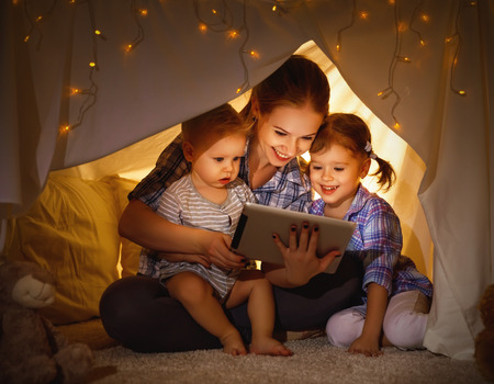 Happy family mother and children playing in tablet  pc in a tent evening in dark