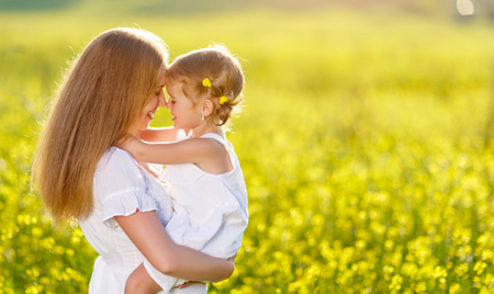 familia abrazo: madre e hija familia feliz hijo se abrazan en las flores amarillas en la naturaleza en verano Foto de archivo