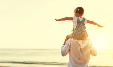 아버지의 날. 아빠와 아이의 딸은 여름 해변에서 함께 야외에서 연주