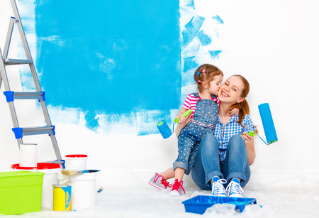 Repair in the apartment. Happy family mother and child daughter  paints the wall with blue paint