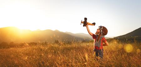 aviador piloto niño con sueños de avión de viajar en verano en la naturaleza en la puesta del sol