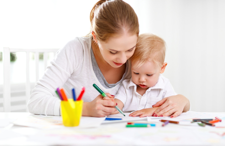 table: Mother with the baby son with colored pencils and laugh