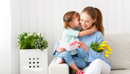 gives: Happy mothers day! Child daughter congratulates moms and gives her a postcard and flowers tulips