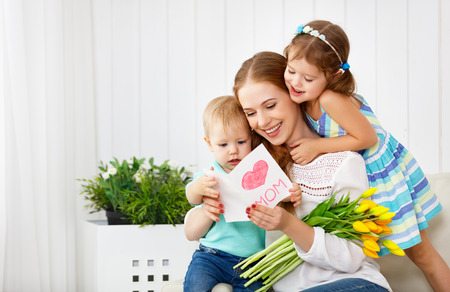 Happy mothers day! Children congratulates moms and gives her a postcard and flowers tulips