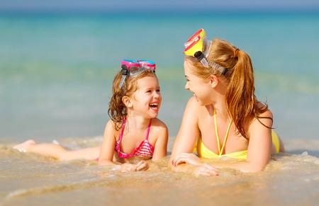 Gelukkig gezin moeder en chid dochter in maskers te zwemmen op het strand in de zomer