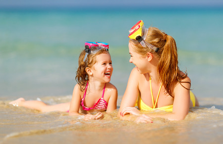 Happy family mother and chid daughter in masks for swimming on the beach in summer