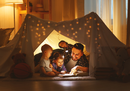 happy family father and children reading a book with a flashlight in a tent at home