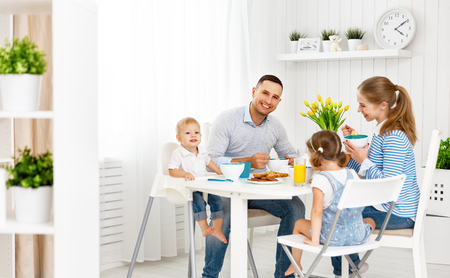 Happy family mother, father and children at breakfast