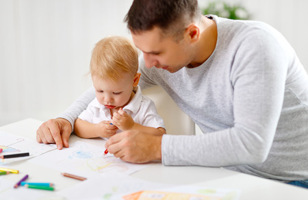 paints: father and baby son paint together with colored pencils