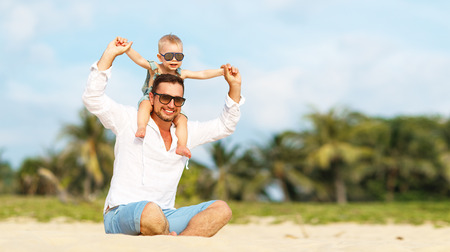 fathers day. Dad and baby son playing together outdoors on a summer beach Stock Photo