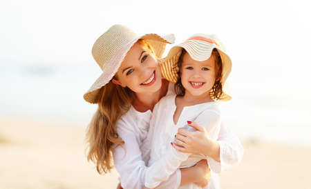 Glückliche Familie am Strand. motherand Kind Tochter umarmen bei Sonnenuntergang Standard-Bild - 74717622