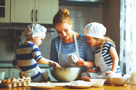 domestic: happy family in the kitchen. mother and  children preparing the dough, bake cookies