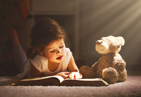 Little child girl is reading a book in evening in dark with a toy bear