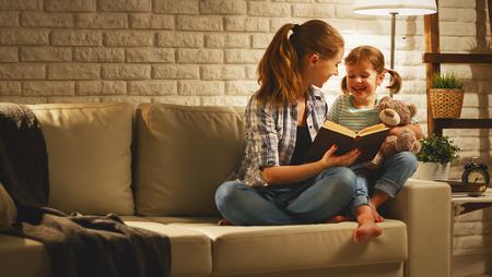 Famiglia prima di andare a letto madre legge al suo bambino figlia libro nei pressi di una lampada in serata