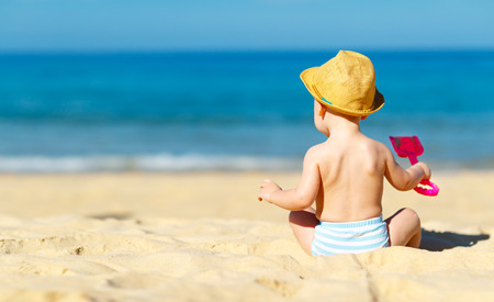 baby sit: baby boy sit back  with  toys and sand on beach Stock Photo
