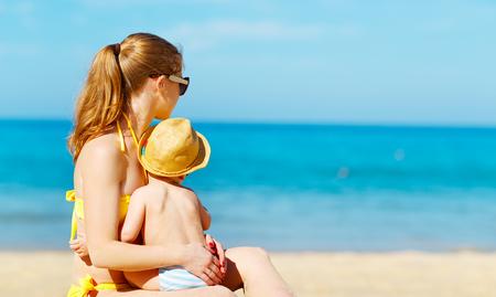 Gelukkig gezin moeder met baby zoon op het strand in de zomer Stockfoto - 75486166