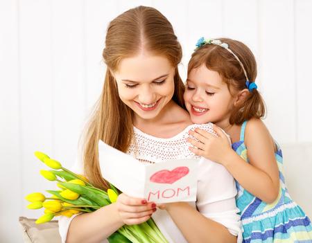 Schönen Muttertag! Kinder Tochter gratuliert Mütter und gibt ihr eine Postkarte und Blumen Tulpen Standard-Bild - 75506287