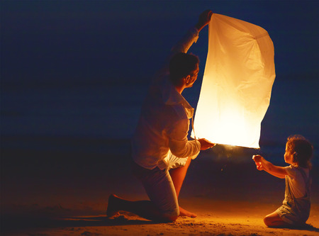 lamp light: Family  father and daughter, send air heavenly flashlight lamp in flight on beach Stock Photo