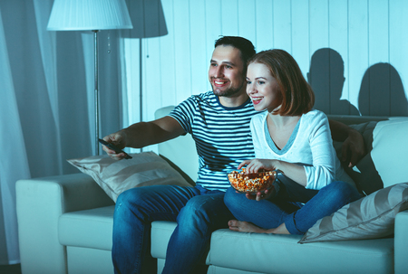 couple on couch: Family couple watching television at home on the sofa