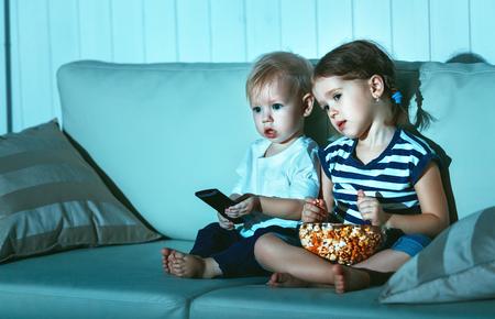 Los niños hermano y hermana viendo la televisión en la noche Foto de archivo - 75750558