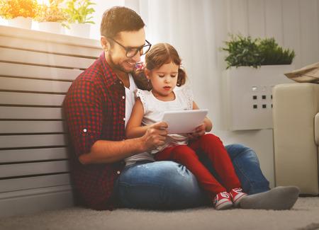 Glückliche Familie Vater und Tochter spielen mit Tablet-Computer zu Hause