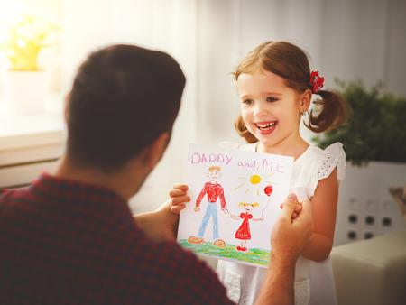 아버지의 날. 아빠에게 휴일 인사말 카드를주고 행복한 가족의 딸