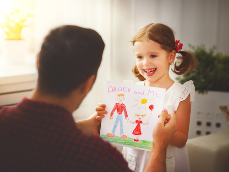 Vaderdag. Gelukkige familie dochter geven papa een wenskaart op vakantie Stockfoto - 76041061