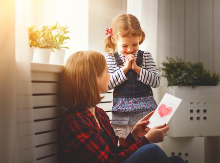 Gelukkige Moederdag! Dochter geeft haar moeder een briefkaart en knuffels