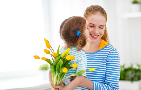 Happy mothers day! Child daughter congratulates moms and gives her a postcard and flowers tulips