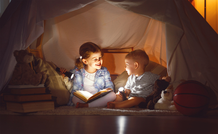 kinderen jongen en meisje leesboek met een zaklamp in de tent 's nachts