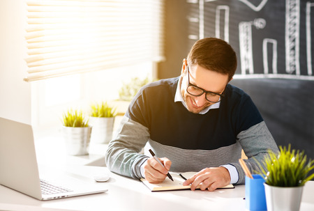 Happy man businessman, freelancer, student working at computer at home and office Stock Photo
