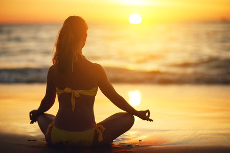 healthy body: woman practices yoga and meditates in the lotus position on the beach