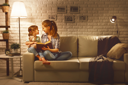 Family before going to bed mother reads to her child daughter book near a lamp in the evening 写真素材