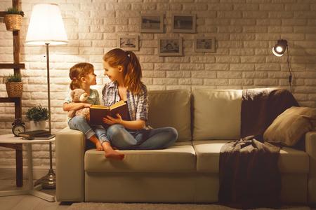 夕方にはランプ近く彼女の子の娘の本に母のベッドに行く前に家族を読み取ります 写真素材