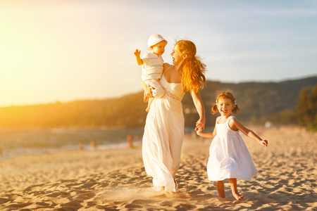 Happy family mother and children on the beach by the sea in summer