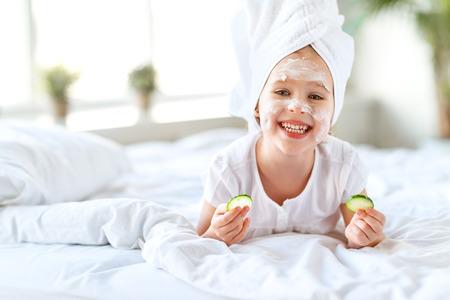 Gelukkig kind meisje in handdoek met masker op gezicht en komkommer Stockfoto