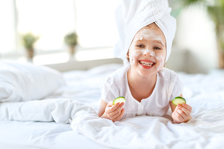 happy child girl in towel with mask on face and cucumber Фото со стока
