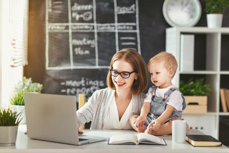 Geschäftsfrau Mutter Frau mit einem Kleinkind arbeitet am Computer Standard-Bild - 77074022