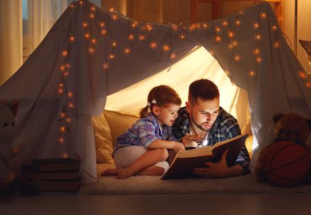 feliz padre de familia y su hija niño que lee un libro con una linterna en una tienda de campaña en el hogar
