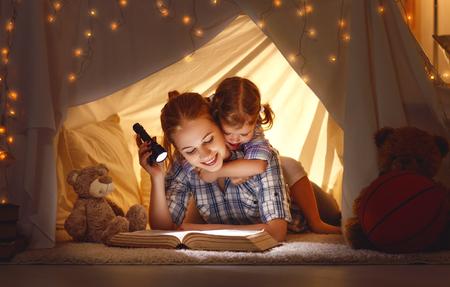 lezen en familiespelletjes in de kindertent. moeder en kind dochter met boek en zaklamp voor het naar bed gaan