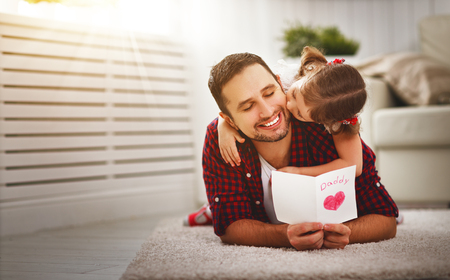 Festa del papà. Famiglia felice figlia bacio papà e dando biglietto di auguri in vacanza Archivio Fotografico - 77074194