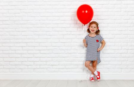 Gelukkig grappig kind meisje met een rode bal in de buurt van een lege witte bakstenen muur Stockfoto