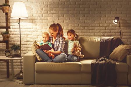 Family voordat je naar bed moeder leest de kinderen een boek over een lamp in de avond