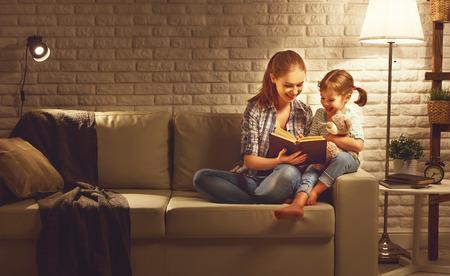 Famille avant de se coucher mère lit à son enfant livre fille près d'une lampe dans la soirée Banque d'images